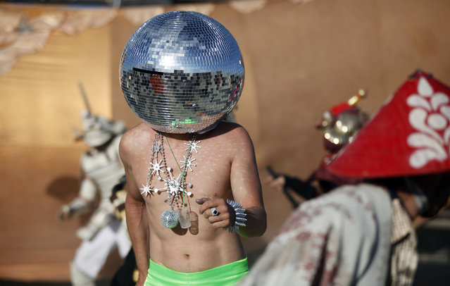 """Ciberfy, his play name, dances at sunrise during the Burning Man 2012 """"Fertility 2.0"""" arts and music festival in the Black Rock Desert of Nevada, August 31, 2012. (Photo by Jim Urquhart/Reuters)"""