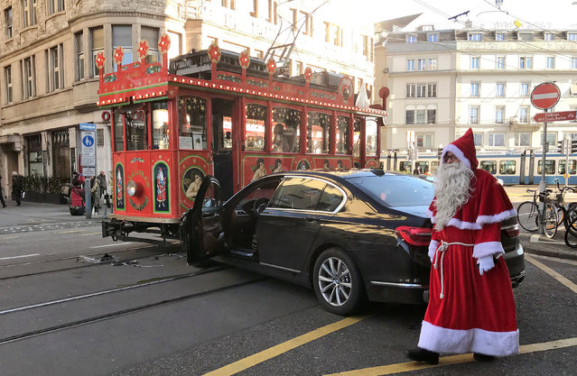 The driver of a Maerlitram (fairy tram), dressed as a Santa Claus, walks past a car which crashed into the tram in Zurich, Switzerland December 7, 2017. (Photo by Angelika Gruber/Reuters)