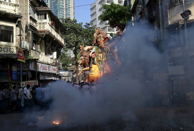 Fireworks explode as an idol of Hindu god Ganesh, the deity of prosperity, is taken through a street on the last day of the ten-day-long Ganesh Chaturthi festival in Mumbai, India, September 27, 2015. (Photo by Danish Siddiqui/Reuters)