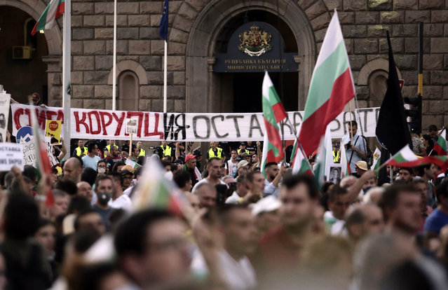 """Protesters carry a poster reading """"Corruption – Resignation"""" during a mass protest in downtown Sofia, Bulgaria, on Wednesday, July 29, 2020. Tens of thousands of people took to the streets Wednesday in cities across Bulgaria for a third consecutive week to demand the resignation of the government and the chief prosecutor. (Photo by Valentina Petrova/AP Photo)"""