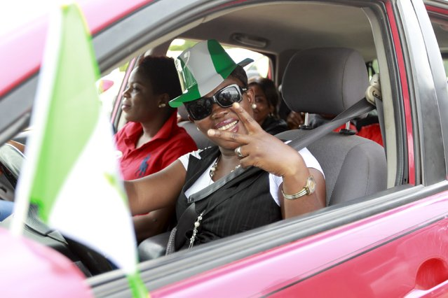 A woman wearing a green and white coloured hat, the colours of Nigeria's national flag, gestures during celebrations for the country's 55th Independence Day in Abuja, Nigeria, October 1, 2015. (Photo by Afolabi Sotunde/Reuters)