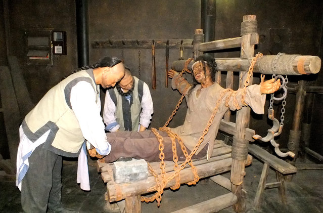 "Wax figures with torture instrument named ""torture-rack"" are seen on October 25, 2014 in Huai'an, Jiangsu province of China. The exhibition, which opened last year at an educational center in the eastern city of Huai'an, includes reenactments of prisoners being hung over a fire, flayed and being tortured on what is known as a ""Tiger Bench"" – pictured above – a Qing dynasty (1644-1912) device that contorted victims' legs and arms in high pressure positions that could break bones or tear apart joints. (Photo by ChinaFotoPress)"