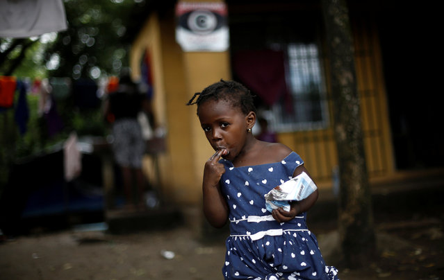 An African migrant child eats ice cream at a makeshift camp at the border between Costa Rica and Nicaragua, in Penas Blancas, Costa Rica, September 7, 2016. (Photo by Juan Carlos Ulate/Reuters)