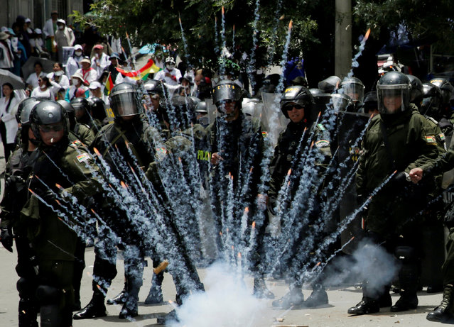 A firecracker explodes next to riot police officers during a protest rally against Bolivia's government new health care policies in La Paz, Bolivia December 27, 2017. (Photo by David Mercado/Reuters)