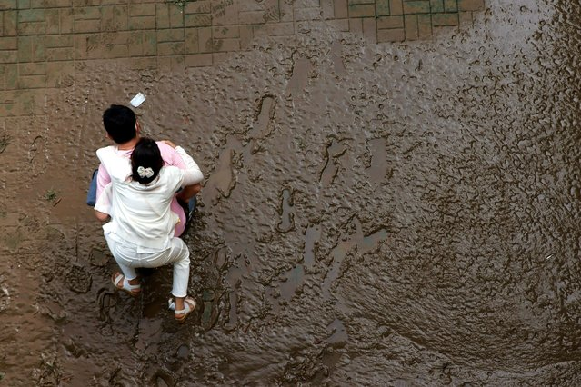 A man crosses a mud-covered trail carrying his wife on his back at a flooded Han River park in Seoul, South Korea, August 4, 2020. (Photo by Kim Hong-Ji/Reuters)
