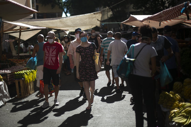 Customers wearing face masks walk at a street market in downtown Rio de Janeiro amidst the coronavirus (COVID-19) pandemic on June 20, 2020 in Rio de Janeiro, Brazil. According to the Brazilian Health Ministry, Brazil has over 1 million positive cases of coronavirus (COVID-19) and more than 48,900 deaths. (Photo by Bruna Prado/Getty Images)