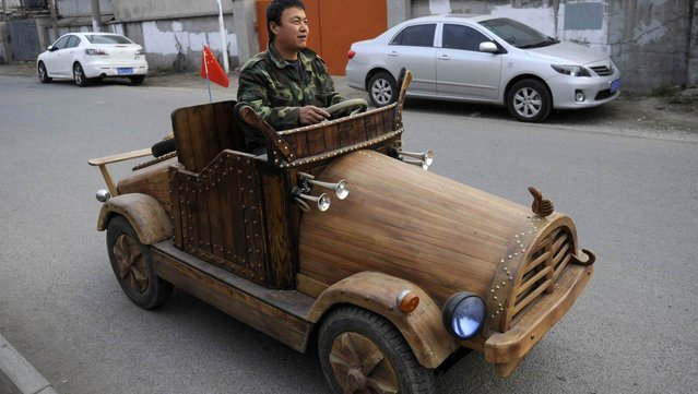 Liu Fulong tests his home-made wooden electronic vehicle in Shenyang, Liaoning province, China, on October 30, 2014. (Photo by Reuters/China Daily)