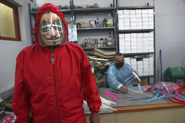An inmate models the protective gear inmates manufacture as fellow inmate Luis Huaman makes face shields at a workshop in the Lurigancho prison, on the outskirts of Lima, Peru, Wednesday, August 19, 2020. Health authorities and inmates look to implement protocols to curb the spread of COVID-19 at the overcrowded prison. (Photo by Martin Mejia/AP Photo)
