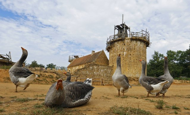 A view of the construction site of the Chateau de Guedelon near Treigny in the Burgundy region of France, September 13, 2016. Blacksmiths, stonemasons and quarry men are hard at work in a Burgundy forest building a 13th-century-style castle using the most basic tools and materials, replicating the methods used hundreds of years ago to better understand them. Forgoing all modern technology, workers use hammers to break stones and forge iron, operate wooden wheels to hoist their materials up to where they are needed, and rely on a quarry for stone, clay and sand as they build up a castle from scratch. Construction on Guedelon Castle in central France began in 1997 after an archaeological survey revealed a medieval fortress hidden inside the walls of nearby Chateau de Saint-Fargeau. Those behind the project hope to answer questions about medieval construction and provide lessons on sustainable building. (Photo by Jacky Naegelen/Reuters)