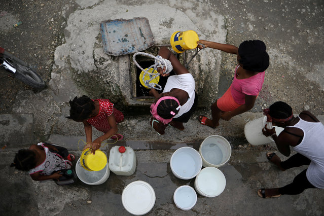 Women fill buckets with water from a reservoir in a street of Port-au-Prince, Haiti, November 11, 2017. (Photo by Andres Martinez Casares/Reuters)