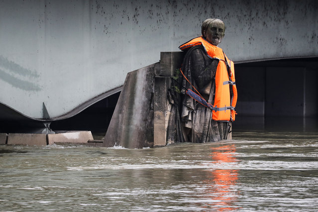 The Zouave statue of the Pont D'Alma bridge standing partially submerged after the River Seine burst its banks in Paris, wears a life jacket put by activits of the Fondation Goodplanet on February 4, 2018. (Photo by Francois Guillot/AFP Photo)