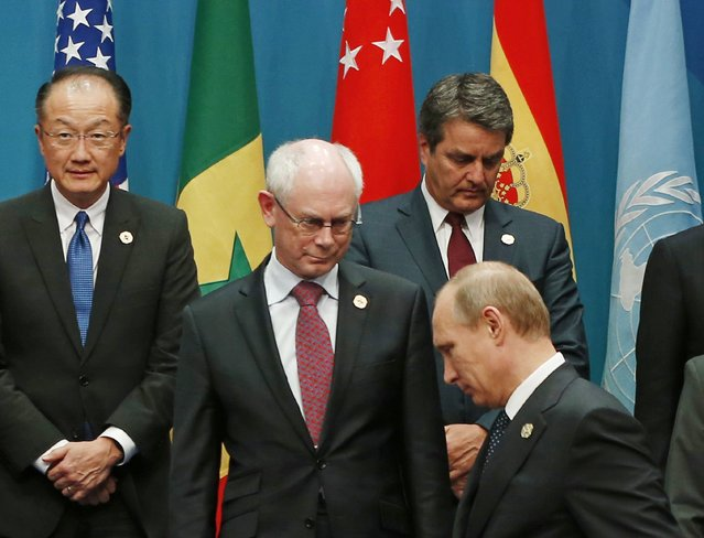 Russian President Vladimir Putin (front) looks for his standing position near European Council President Herman Van Rompuy (2nd L) during a group photo of G20 leaders and representatives of partner groups at the G20 summit venue in Brisbane November 15, 2014. (Photo by Jason Reed/Reuters)
