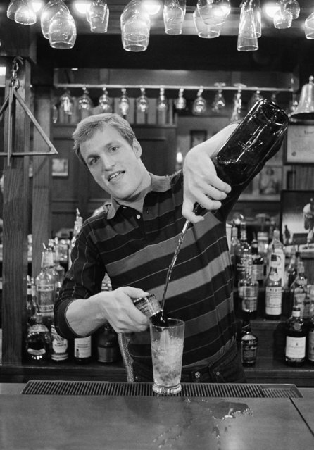 """Actor Woody Harrelson in character as Woody Boyd, the Indiana boy who becomes bartender in TV's """"Cheers"""", December 16, 1985, Los Angeles, Calif. Harrelson has very little acting experience but found himself replacing the late Nicholas Colasanto in the hit series. (Photo by Mike Tweed/AP Photo)"""