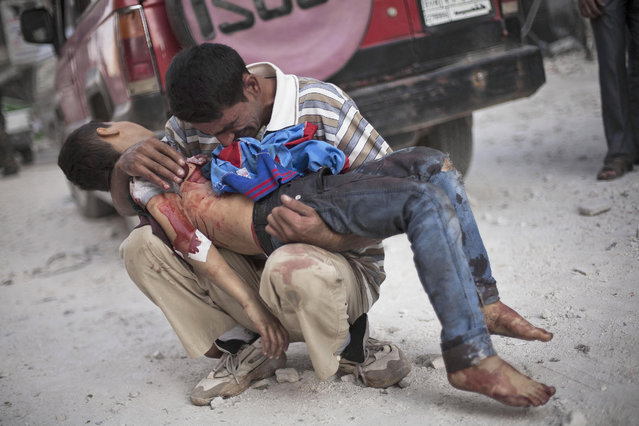 A Syrian man cries while holding the body of his son, killed by the Syrian Army, near Dar El Shifa hospital in Aleppo, Syria, Wednesday, October 3, 2012. (Photo by Manu Brabo/AP Photo)