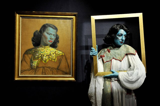 """Cabaret artist Tricity Vogue whose act """"Blue Lady"""" is inspired by South African settled Russian artist Vladimir Tretchikoff, as she stands next to his work  """"Chinese Girl"""" which will go on sale during Bonhams' South African art sale on March 20th and will be sold for an estimated £300,000 to £500,00. (Photo by Nick Ansell/PA Wire)"""