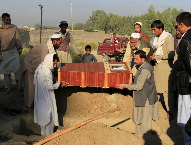 Afghan men bury a boy who was killed after an earthquake, in Behsud district of Nangarhar province, Afghanistan October 27, 2015. Rescuers on Tuesday rushed to deliver relief aid to victims of a massive earthquake that hit northern Afghanistan and Pakistan. (Photo by Reuters/Parwiz)