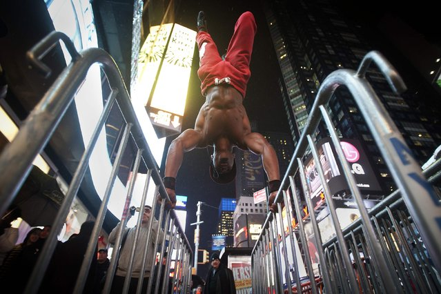 A man who gave his name as Wildcat works out on NYPD crowd control barricades in the rain in Times Square in New York, December 1, 2014. Wildcat says he works out in public places to encourage others to get healthy without the need for fancy equipment. (Photo by Carlo Allegri/Reuters)