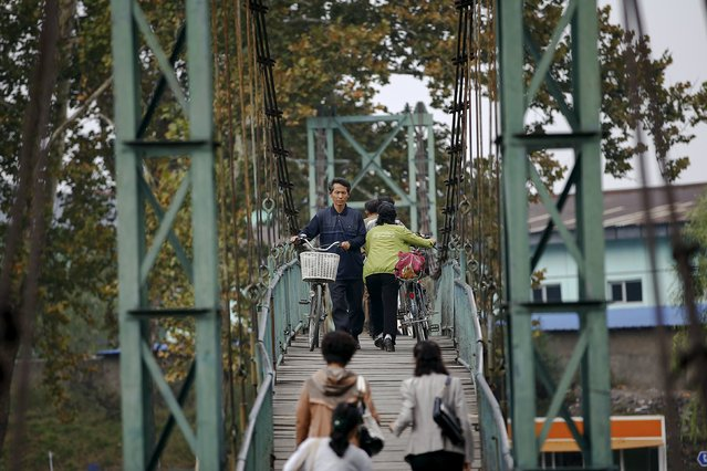 People push their bicycles over a bridge in central Pyongyang October 8, 2015. (Photo by Damir Sagolj/Reuters)