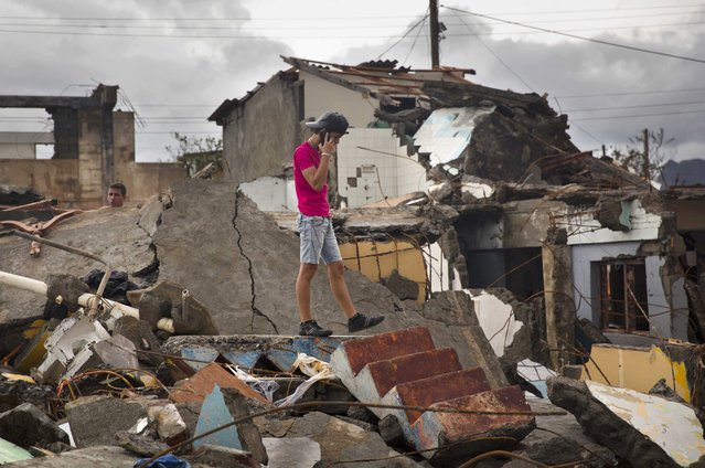 A man talks on his cell while searching for belongings amid the rubble of his home destroyed by Hurricane Matthew in Baracoa, Cuba, Wednesday, October 5, 2016. (Photo by Ramon Espinosa/AP Photo)