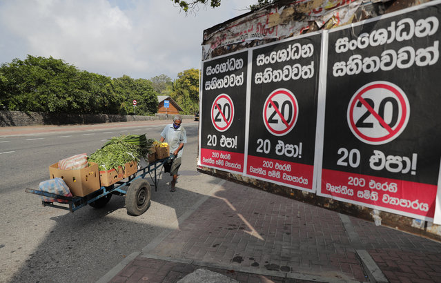"""A Sri Lankan vegetable seller pushes his cart past posters against a proposed constitutional amendment that would consolidate power in the president's hands in Colombo, Sri Lanka, Tuesday, October 20, 2020. Sinhalese reads """"No to 20 even with amendments"""". (Photo by Eranga Jayawardena/AP Photo)"""