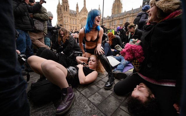 "Demonstrators take part in a mass ""face-sitting protest"" outside the Houses of Parliament in central London on December 12, 2014, as they protest against changes to p*rnography regulations. (Photo by Leon Neal/AFP Photo)"