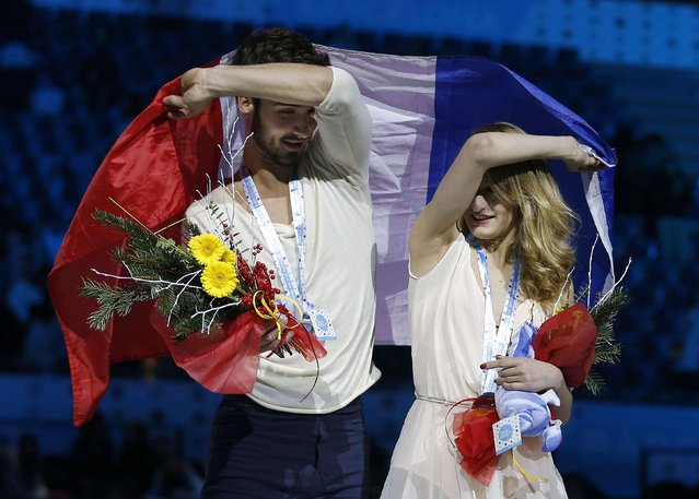 Bronze medallists Gabriella Papadakis and Guillaume Cizeron of France wave their national flag during an award ceremony after placing third in the Ice Dance final competition at the ISU Grand Prix of Figure Skating final in Barcelona December 13, 2014. (Photo by Gustau Nacarino/Reuters)