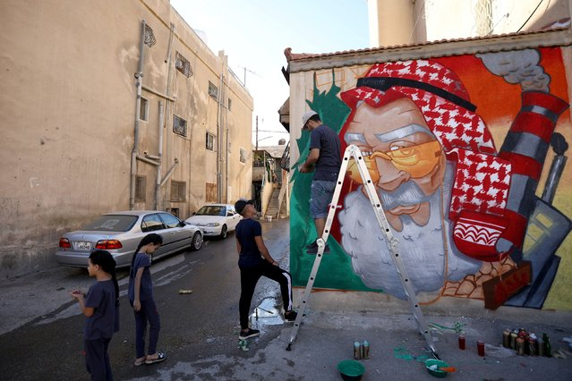 Jordanian artist, Yazan Bahar, works on his mural on a building as part of the Baladk festival, which includes murals across Amman all with a message encouraging people to protect the environment, Jordan, October 13, 2020. (Photo by Muhammad Hamed/Reuters)