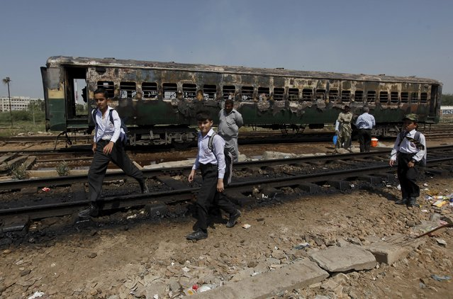 Students walk past the doused car of a train which caught fire as they head home along a railway track at Cantonment railway station in Karachi, Pakistan, October 9, 2015. There were no casualties reported. (Photo by Akhtar Soomro/Reuters)