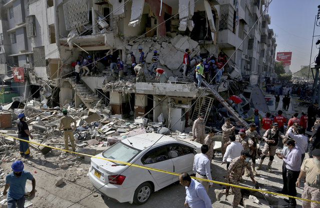 Pakistan's troops and rescue workers look for survivors in the rubble following the explosion, in Karachi, Pakistan, Wednesday, October 21, 2020. Police and rescuers say a powerful blast has ripped through a multistory building in Pakistan's southern port city of Karachi. (Photo by Fareed Khan/AP Photo)