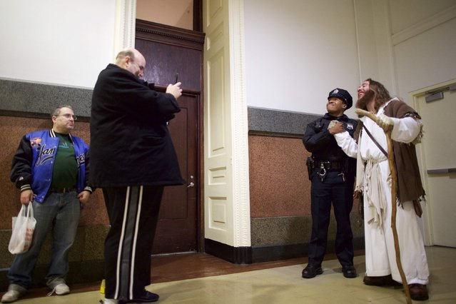 "A police officer asked to take a photograph with Michael Grant, 28, ""Philly Jesus"", inside Philadelphia City Hall in Philadelphia, Pennsylvania December 14, 2014. (Photo by Mark Makela/Reuters)"