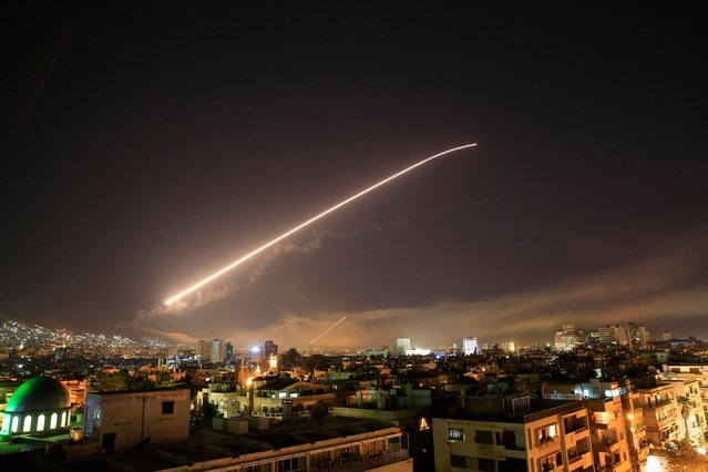 The Damascus sky lights up missile fire as the U. S. launches an attack on Syria targeting different parts of the capital early Saturday, April 14, 2018. Syria' s capital has been rocked by loud explosions that lit up the sky with heavy smoke as U. S. President Donald Trump announced airstrikes in retaliation for the country' s alleged use of chemical weapons. (Photo by Hassan Ammar/AP Photo)