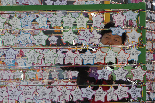 A woman hangs on a paper note to wish for her child's success in the college entrance exams at the Jogyesa Buddhist temple in Seoul, South Korea, Thursday, December 3, 2020. (Photo by Ahn Young-joon/AP Photo)