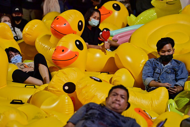 Pro-democracy protesters rest on large inflatable ducks during an anti-government rally at Lat Phrao intersection in Bangkok on December 2, 2020. (Photo by Lillian Suwanrumpha/AFP Photo)