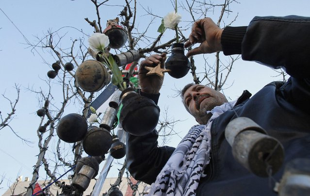 A Palestinian man decorates a tree with spent tear gas canisters that he said were fired by Israeli troops during clashes with Palestinian protesters, at Manger Square, ahead of Christmas, in the West Bank city of Bethlehem December 23, 2014. (Photo by Ammar Awad/Reuters)