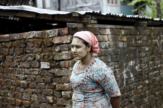 A Muslim Rohingya woman wears Thanakha on her face as she walks at the Aung Minglar quarter in Sittwe October 29, 2015. (Photo by Soe Zeya Tun/Reuters)