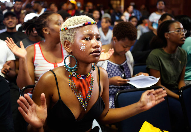 A student from the University of Cape Town claps her hands as she and other students chant and sing as they gather to discuss possible student fee increases at there campus in Cape Town, South Africa, Monday, September 19, 2016. (Photo by Schalk van Zuydam/AP Photo)