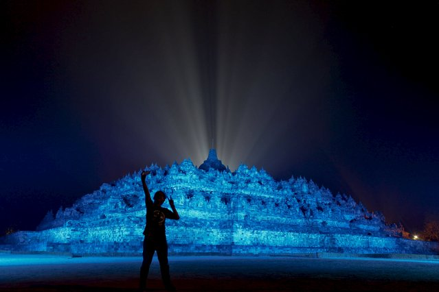A visitor takes a picture as the 9th century Borobudur temple is illuminated with blue light to honour the 70th anniversary of the United Nations in Magelang, Central Java, October 24, 2015 in this photo taken by Antara Foto. (Photo by Andreas Fitri Atmoko/Reuters/Antara Foto)