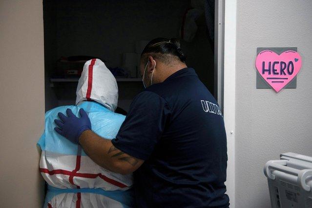 Alan Murcia comforts his wife, Corina Murcia, inside a coronavirus disease (COVID-19) unit at United Memorial Medical Center in Houston, Texas, U.S., December 12, 2020. (Photo by Callaghan O'Hare/Reuters)