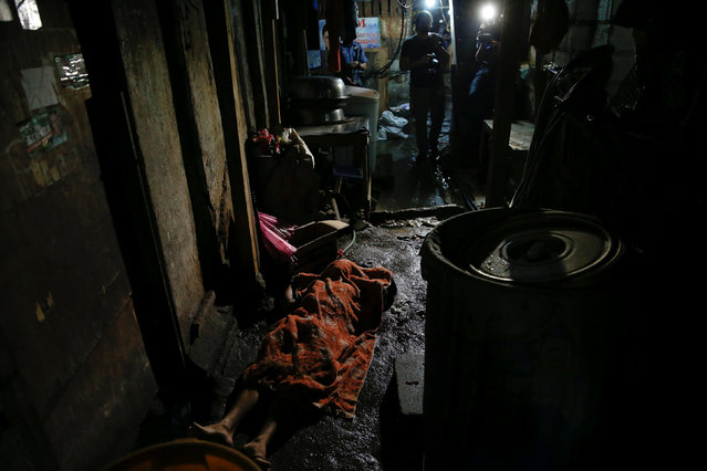 The body of a man killed is covered with a blanket inside a slum in port area of Manila, Philippines early October 21, 2016. (Photo by Damir Sagolj/Reuters)
