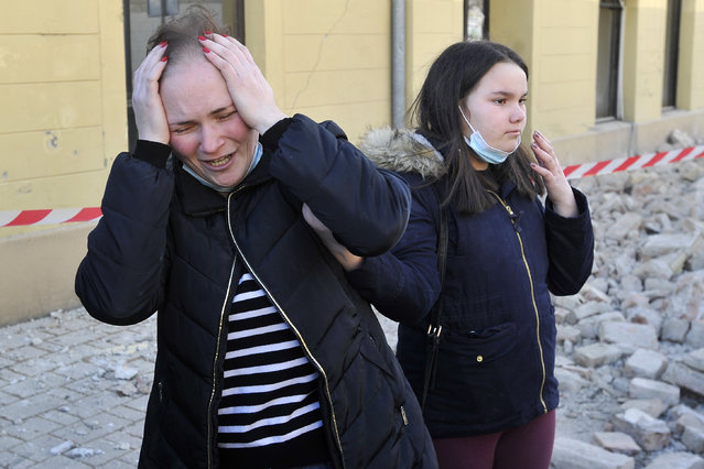 A woman reacts next to buildings damaged in an earthquake in Petrinja, Croatia, Tuesday, December 29, 2020. A strong earthquake has hit central Croatia and caused major damage and at least one death and 20 injuries in a town southeast of the capital Zagreb. (Photo by AP Photo/Stringer)