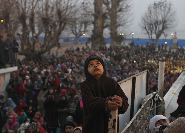 A Kashmiri Muslim boy holds onto a fence as he looks at a relic of Prophet Mohammad being displayed to devotees during the festival of Eid-e-Milad at Hazratbal shrine on the cold winter morning in Srinagar January 4, 2015. (Photo by Danish Ismail/Reuters)