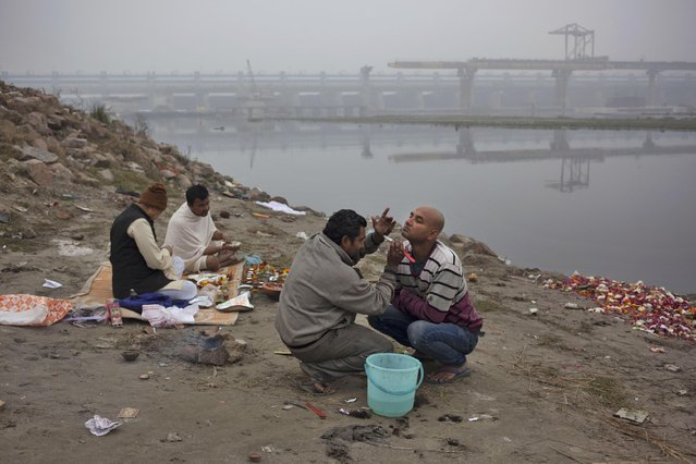 An Indian man gets a shaves as rest pray on the banks of the Yamuna River on a foggy morning in New Delhi, India, Wednesday, January 7, 2015. Several parts of north India shivers as severe cold wave conditions and fog has thrown normal life out of gear, disrupting rail, road and air traffic. (Photo by Tsering Topgyal/AP Photo)
