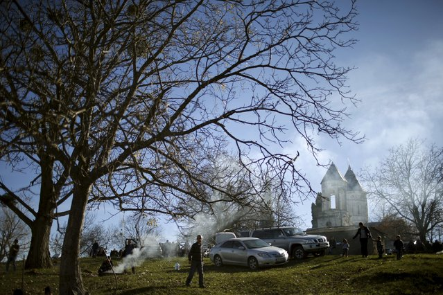 People gather around a church during St. George's Day celebration in the village of Ikalto, Georgia, November 23, 2015. (Photo by David Mdzinarishvili/Reuters)