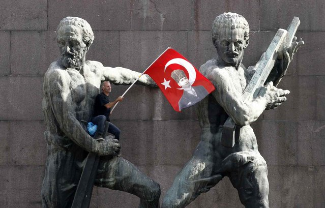 A demonstrator waves Turkey's national flag as he sits on a monument during a protest against Turkey's Prime Minister Tayyip Erdogan and his ruling AK Party in central Ankara June 2, 2013. Erdogan accused Turkey's main secular opposition party on Sunday of stirring a wave of anti-government protests, as tens of thousands regrouped in Istanbul and Ankara after a lull and trouble flared again in the capital. Police used tear gas on protesters in Ankara but the clashes were relatively minor compared with major violence in Turkey's biggest cities on the previous two days. (Photo by Umit Bektas/Reuters)