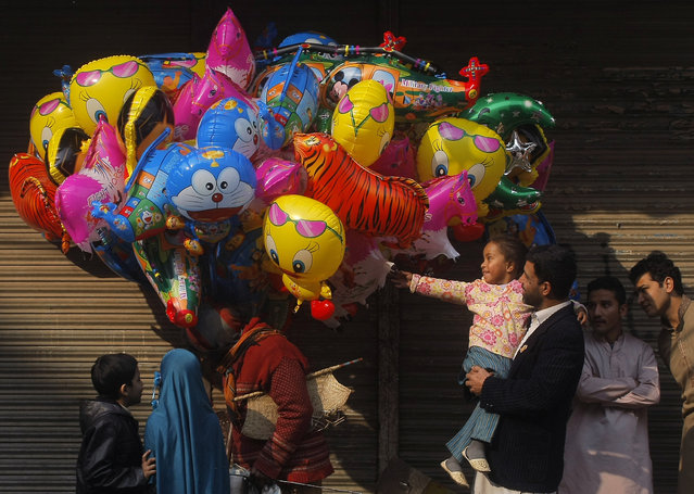 Pakistanis shop for cartoon-shaped balloons from a vendor standing on a street leading to a rally marking the birthday of Islam's Prophet Muhammad in Peshawar, Pakistan, Sunday, January 4, 2015. (Photo by Muhammad Sajjad/AP Photo)