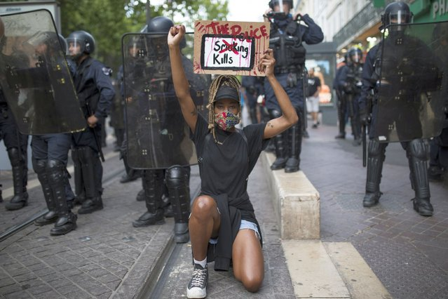 """A protester kneels in front of French riot police with a sign that reads """"The Police Kills"""" in Marseille, southern France, Saturday, June 6, 2020, to protest against the recent death of George Floyd. Floyd, a black man, died after he was restrained by police officers May 25 in Minneapolis, that has led to protests in many countries and across the U.S. Further protests are planned over the weekend in European cities, some defying restrictions imposed by authorities due to the coronavirus pandemic. (Photo by Daniel Cole/AP Photo)"""