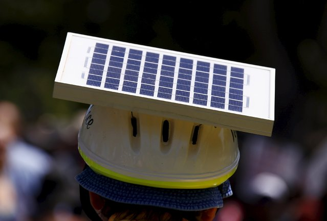 A cyclist wears a helmet with a solar panel attached as he participates in a march the day before the Paris World Climate Change Conference, along the main street of Adelaide, South Australia November 29, 2015. (Photo by David Gray/Reuters)