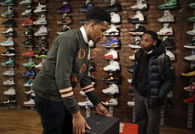In this January 12, 2015 photo, Chase Reed, left, boxes up a pair of shoes for a customer, Chaise Mack, at Sneaker Pawn in the Harlem section of New York. Chase and his father opened Sneaker Pawn looking to capitalize on America's multi-billion dollar athletic footwear market and the high prices sneakers can get being re-sold. (Photo by Seth Wenig/AP Photo)