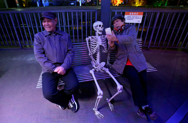 A woman takes a selfie with a fake skeleton next to her husband ahead of a Halloween parade at Happy Valley park in Beijing, China October 31, 2016. (Photo by Jason Lee/Reuters)