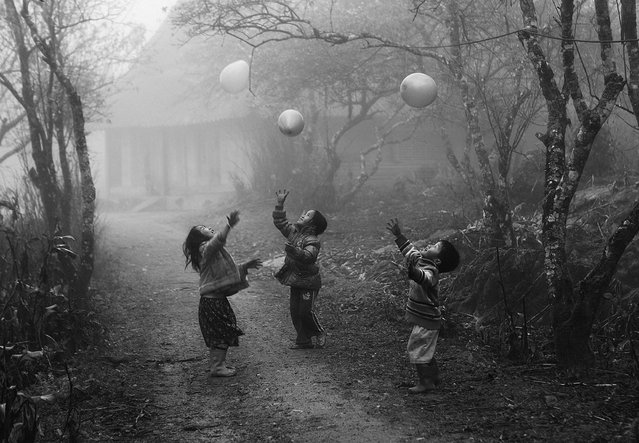 """Second Place Winner: My Balloon"". H'mong children play with their balloons on a foggy day in Moc Chau, Son La province, Vietnam; photographed January 2012. National Geographic contributing photographer Alexandra Avakian, one of this year's judges, shares her thoughts on the second place winner: This picture is like a dream, and it's timeless not only because it's black and white and there's no sense of modernity, but also because it depicts an activity that children everywhere on the planet do with balloons. The fog and soft background make it feel like a memory. It's every bit as good as the photographs in the seminal black-and-white photo book, ""The Family of Man"". Sometimes the best scenes to shoot are not in the obvious places for travelers but can be found anywhere from a far-flung location – such as this remote Hmong village – to just the around the corner from a big event. (Photo and caption by Vo Anh Kiet/National Geographic Traveler Photo Contest)"